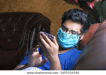 Man is wearing mask to prevent the infectious and using smart phone  #1695554140