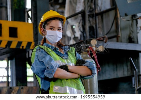 Factory woman worker or technician with hygienic mask stand with confident action sometime as engineer in workplace during concern about public health of corona virus pandemic in people. #1695554959