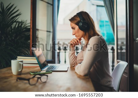 Concentrated student girl learning online having video call via laptop computer sitting at home interior near open balcony, female entrepreneur working remotely from home office using modern computer #1695557203