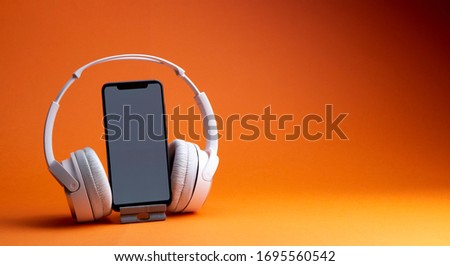 White headphones with smartphone mockup, isolate on orange, music online concept. #1695560542