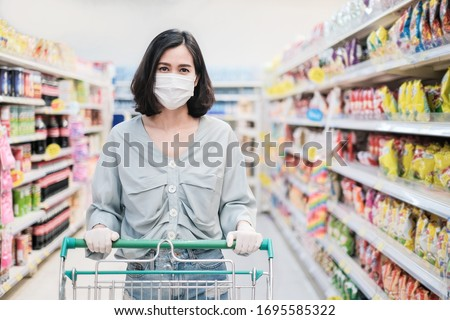 Asian woman wearing face mask and rubber glove push shopping cart in suppermarket departmentstore. Girl choosing, looking grocery things to buy at shelf during coronavirus crisis or covid19 outbreak. #1695585322