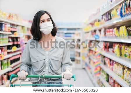 Asian woman wearing face mask and rubber glove push shopping cart in suppermarket departmentstore. Girl choosing, looking grocery things to buy at shelf during coronavirus crisis or covid19 outbreak. #1695585328