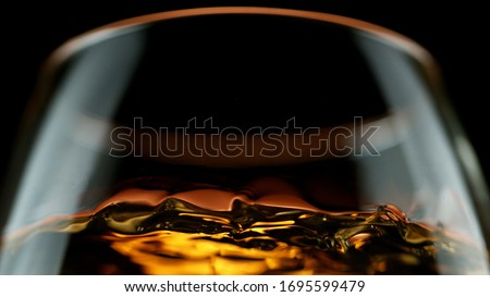 Detail of cognac in glass isolated on black background Royalty-Free Stock Photo #1695599479