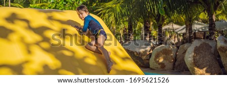 Cute boy runs an inflatable obstacle course in the pool BANNER, LONG FORMAT #1695621526