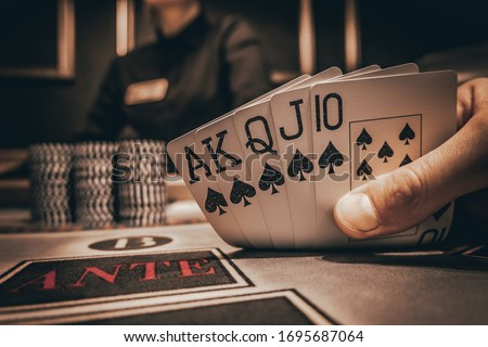 Poker Hands / Royal Flush. Five playing cards - the poker royal flush hand. Royal Flash, card deck, poker royal flash on cards and poker chips on green casino table. success in gambling. soft focus Royalty-Free Stock Photo #1695687064