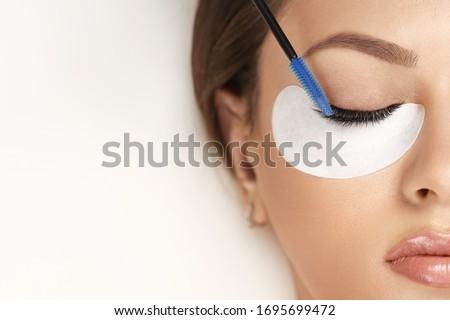 Eyelashes extensions. Fake eyelashes. Eyelash extension procedure.Close up portrait of woman eye with long eyelashes. Professional stylist lengthening female lashes. Master and client in beauty salon. #1695699472