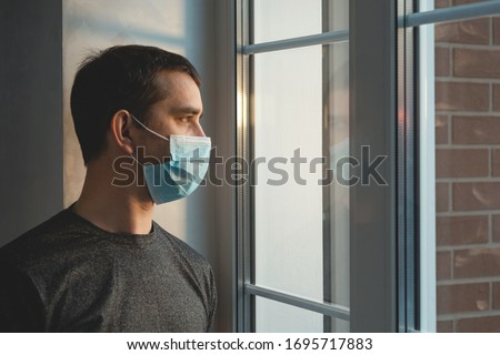 Quarantine self-isolation. Sad young man in a medical mask who looks out the window through the window. Infected man in medical mask on self-isolation looks at the street through the window of a house #1695717883