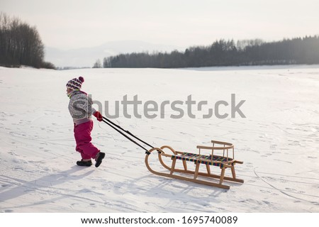 cute ittle girl haveing fun in a snow during christmas winter holiday on a sleigh. Little girl enjoy a sleigh ride. Child sledding. Toddler kid riding a sledge. Children play outdoors in snow.