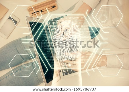 Double exposure of woman hands working on computer and fingerprint hologram drawing. Top View. Digital Security concept. #1695786907