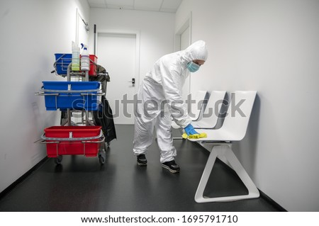 Alert Corona Virus or Covid-19. Cleaner with full protective suit, masks and gloves cleans, disinfects and sanitizes the waiting room of a hospital, clinic or ublic place. Cleaning of chairs. Royalty-Free Stock Photo #1695791710