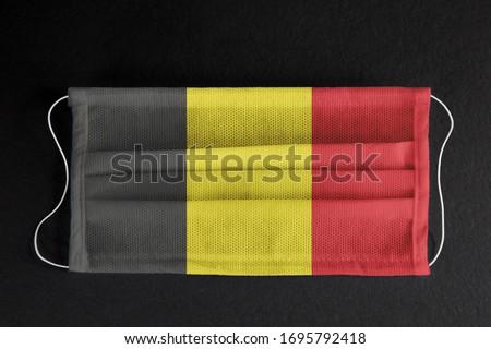 Coronavirus Covid-19 in Belgium. Flag of Belgium printed on medical mask on black background.  Belgium healthcare concept. Spread of corona virus in Europe. #1695792418