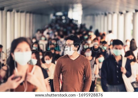 Asian man walking and standing between Crowd of blurred unrecognizable business people wearing surgical mask for prevent coronavirus Outbreak in rush hour working day at Bangkok transportation Royalty-Free Stock Photo #1695928876