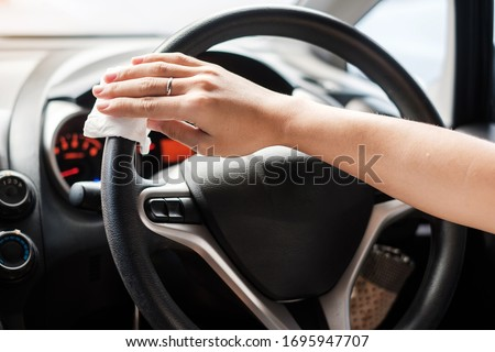 woman hand cleaning on steering wheel in his car, against Novel coronavirus or Corona Virus Disease (Covid-19). Antiseptic, Hygiene and Healthcare concept Royalty-Free Stock Photo #1695947707
