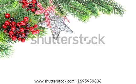 Christmas compositionon with green fir branches, red holly berries and silver star shaped christmas bauble are isolated on a white background, with space for texta white background #1695959836