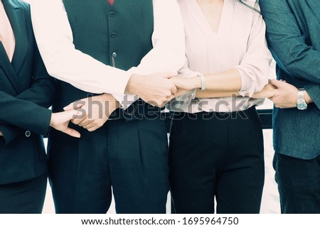Professional business people standing and holding each other hands in the meeting after agreement signed for good collaboration of their new projects. Successful teamwork and work cooperation concept #1695964750