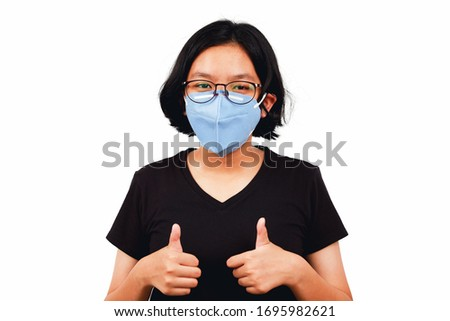 Young girl wear mask and thump up to flighting corona virus or Covid-19 #1695982621