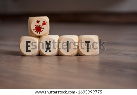 Cubes and dice with corona virus icons and exit strategy on wooden background #1695999775