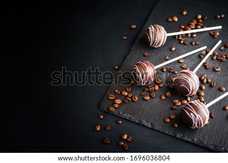 Delicious dessert with chocolate and milk cream on a stick with an atal tape. Cake pops on a slate board on a black background with coffee beans. Royalty-Free Stock Photo #1696036804