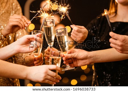Women clinking glasses of tasty champagne at party #1696038733