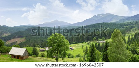 Mountain landscape with outbuildings and hayfields on meadow among the forest on a foreground against the background of distant ridges in the Carpathian Mountains, panoramic view Royalty-Free Stock Photo #1696042507