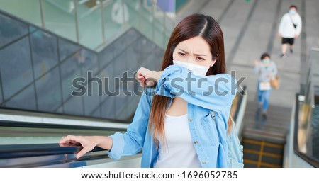 Asian woman coughs in her elbow and keep social distancing from other people with surgical face mask protection - she commutes in the metro or train station #1696052785