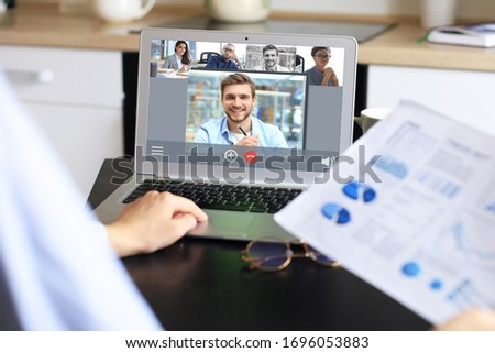 Business woman talking to her colleagues in video conference. Business team working from home using laptop. #1696053883