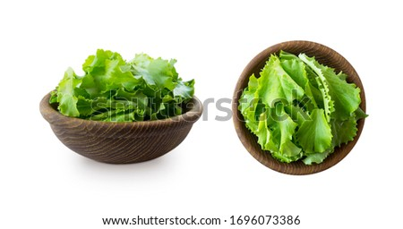 Young lettuce leaves in wooden bowl. Top view. Lettuce isolated on a white background. Green lettuce with copy space for text. lettuce leaves isolated on white. Salad from different angles on white. #1696073386