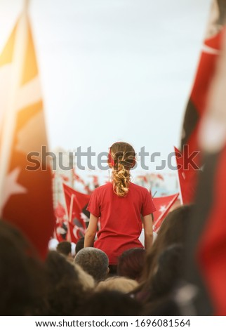 Izmir, Turkey - October 29: A girl between Turkish Flags at Celebrations of Republic day of Turkey. #1696081564
