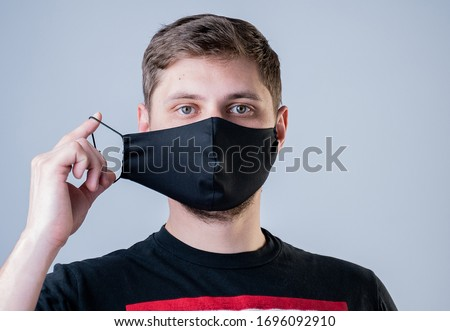Man puts on a face mask. Black stylish face mask during a pandemic virus crown. Handmade cotton face mask for protection against viruses and bacteria. #1696092910