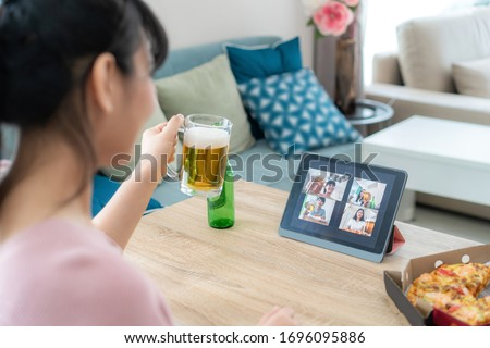 Asian woman virtual happy hour meeting party and drinking alcohol beer online together with her friend in video conference with digital tablet for a online meeting in video call  #1696095886
