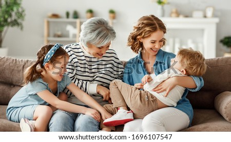 Grandmother and mother hugging and tickling laughing boy while sitting on couch and playing with children on weekend day at home Royalty-Free Stock Photo #1696107547