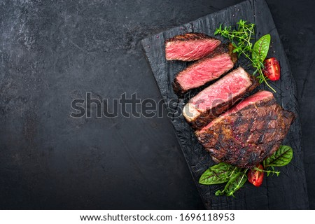 Barbecue dry aged wagyu entrecote beef steak with lettuce and tomatoes as top view on an old charred wooden board with copy space left  #1696118953