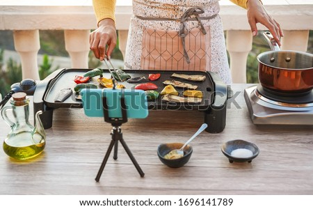 Young woman chef cooking outdoor while streaming online for webinar masterclass lesson at home - Female making videos preparing vegetarian meal on patio terrace - Food concept - Focus on hands #1696141789