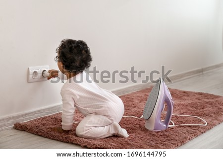 Little African-American baby playing with socket and iron at home. Child in danger Royalty-Free Stock Photo #1696144795