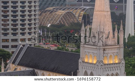 St. Andrew's Cathedral aerial day to night transition view. It is an Anglican cathedral in Singapore, the country's largest cathedral. Skyscrapers on a background