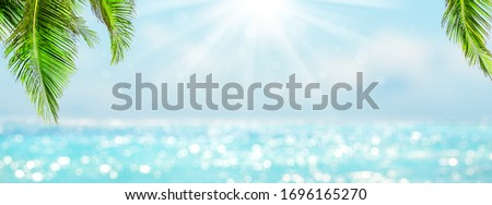 Panorama of blurred blue sky and sea with bokeh light and leaves of coconut palm tree. Landscape of tropical summer. Summer vacation concept.