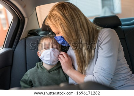 Children and mom in car quarantine  at the season of the COVID-19 (corona-virus) with  surgical masks #1696171282