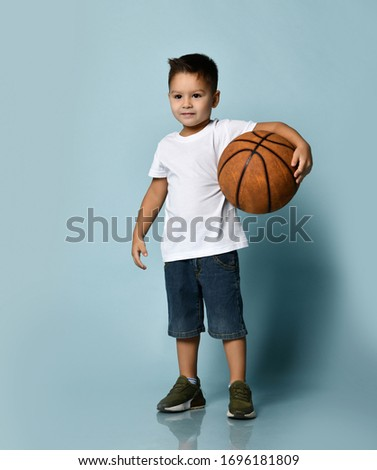 Little brunet kid in white t-shirt, denim shorts and khaki sneakers. Holding basketball ball, smiling, posing against blue studio background. Childhood, fashion and sport. Full length, copy space