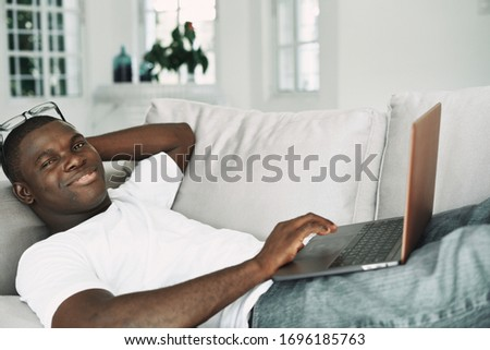 A man of African appearance at home on the couch in front of a laptop relaxing communication #1696185763
