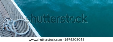Mooring cable on the pier. Сloseup of wooden cleats with nautical moored ropes, blue sea. Extra copy space. Royalty-Free Stock Photo #1696208065