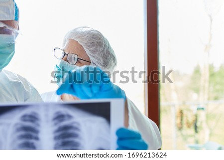 Two doctors analyze pneumonia of Covid-19 patient on x-ray in hospital during coronavirus epidemic #1696213624