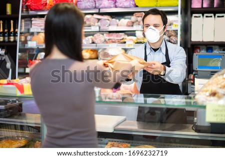 Smiling shopkeeper serving a customer while wearing a mask, coronavirus pandemic concept #1696232719