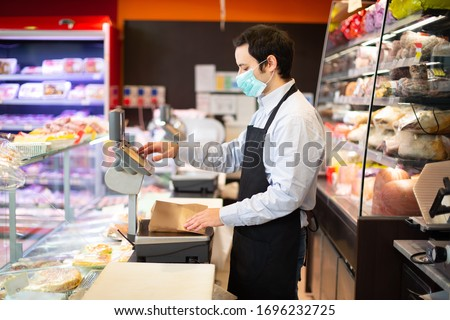 Shopkeeper running his business while wearing a mask, coronavirus pandemic concept #1696232725