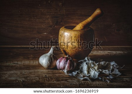 photo garlic in kitchen with mortar on wooden background