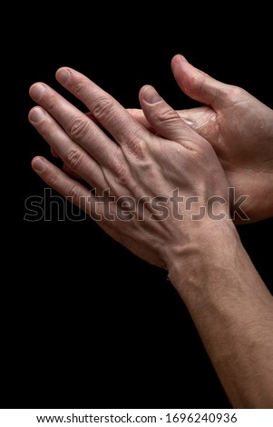 Young man is washing his hands with bubly soap on his hands on a black background, closeup #1696240936