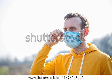 Close up portrait of a man outdoor in a surgical mask with rubber ear straps. Typical three-layer surgical mask for covering the mouth and nose. Bacteria mask procedure. Protection concept.