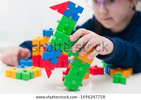 Caucasian little girl with glasses playing with colorful toy blocks on white desk or table. Small kid blurred on background. Concept of homeschooling or stay at home activities. #1696247758