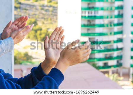 Family applauding medical staff from their balcony. People in Spain clapping on balconies and windows in support of health workers during the Coronavirus pandemic #1696262449