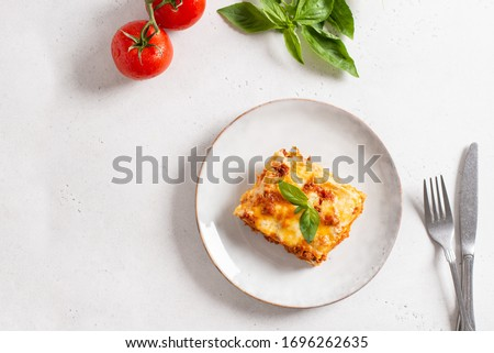 Piece of tasty hot lasagna served with a basil leaf on a gray plate. Italian cuisine, menu, recipe. Homemade meat lasagna. Copy space for text, top view #1696262635