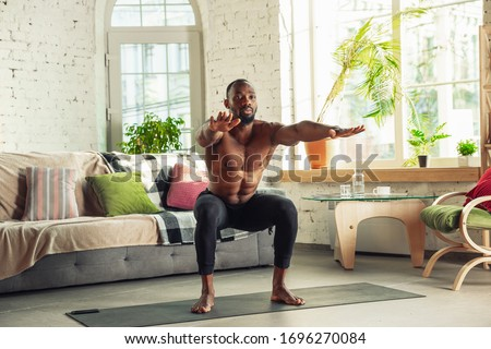 African-american man teaching at home online courses of fitness, aerobic, sporty lifestyle while being quarantine. Getting active while isolated, wellness, movement concept. Training, sit-ups. #1696270084